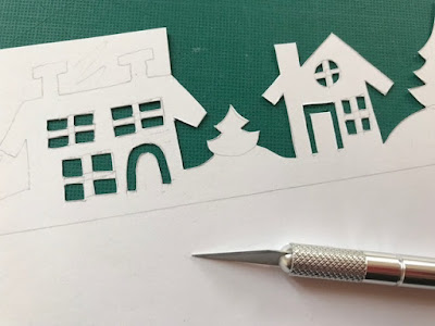 Using a scalpel to cut out a winter scene