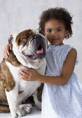 A girl poses for a photo with her pet bulldog