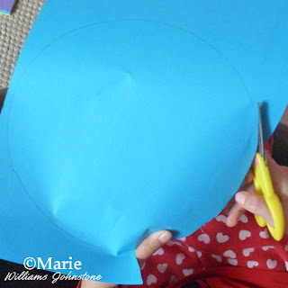 child cutting out a blue circle of paper with kid friendly scissors