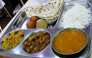 Several curries, rice, naan, chapatti