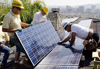 Workers install solar panels. (Credit: Associated Press) Click to Enlarge.