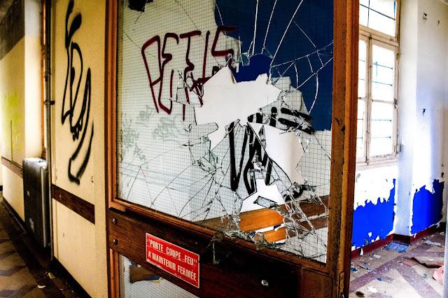 photo d une porte cassée vitre cassée du sanatorium abandonné