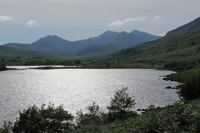 A hazy view of Snowdon, looking along the lake, which shines in the sunlight.