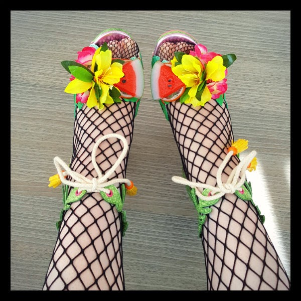 close up of feet wearing fishnet tights and rope tied ankle strap green shoes with fruit and flower embellishments
