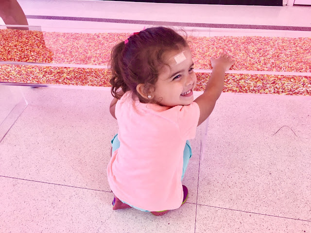 Little girl kneeling and smiling at a bench full of sprinkles
