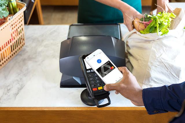 Ein Smartphone wird an ein Kartenlesegerät zum Bezahlen gehalten