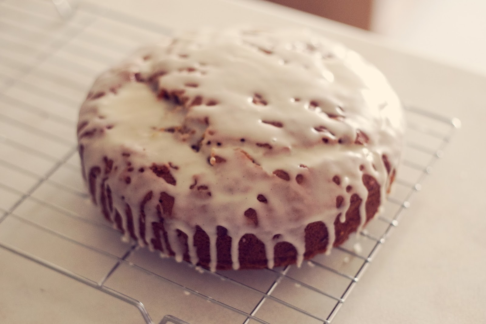 Carrot cake on cooling rack dripping in icing.