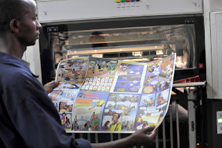 A printer inspects an uncut comic sheet