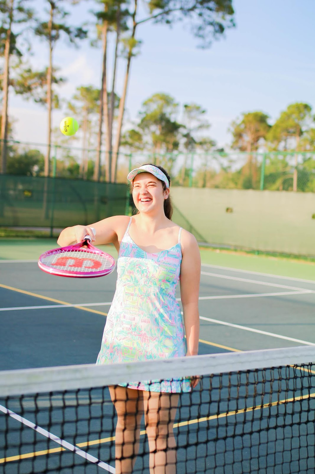 Brunette girl wearing Lilly Pulitzer tennis dress and hat and playing tennis at tennis courts with Wilson tennis racket