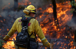 A firefighter works to defend homes from the approaching wildfire in Sonoma, Calif., on Saturday. (Credit: Jim Urquhart/Reuters) Click to Enlarge.