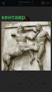 На стене находится барельеф в виде кентавра и мужчина с ним в борьбе