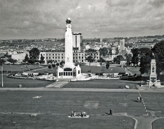 Black and white photograph of a monument and skyline from a slightly raised position with tiny people in the foreground on an open space.