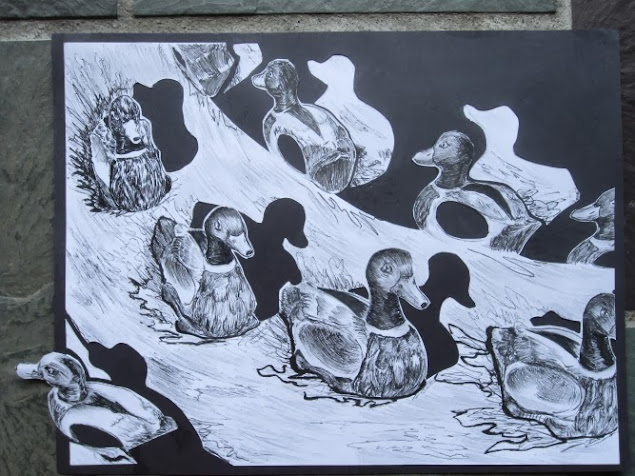 paper cutout drawing depicting swimming ducks