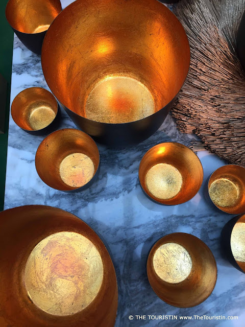Nine different sized gold-coloured bowls on a marble table.