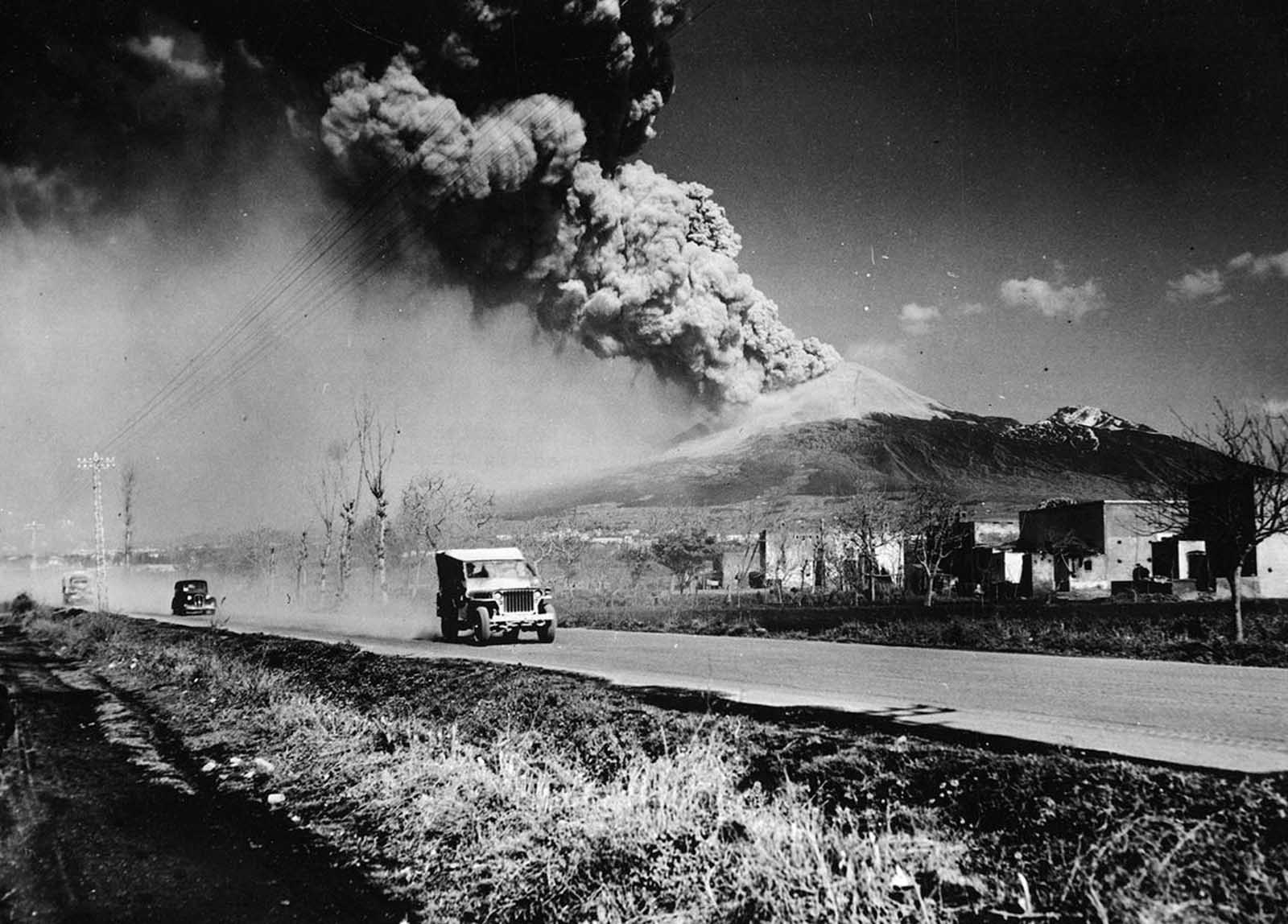 Mt. Vesuvius spewing ash into the sky, erupting as a U.S. Army jeep speeds by shortly after the arrival of the Allied forces in Naples, Italy in 1944.