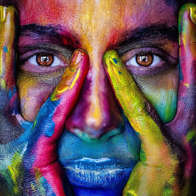 a woman with their faces painted in different colors showing the creativity of the artists