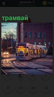 В вечернее время по рельсам в городе идет освещенный трамвай