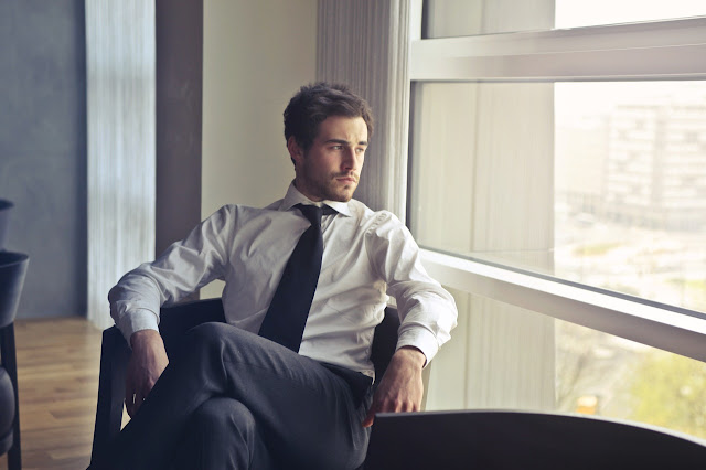 Young business man looking out window, personal development