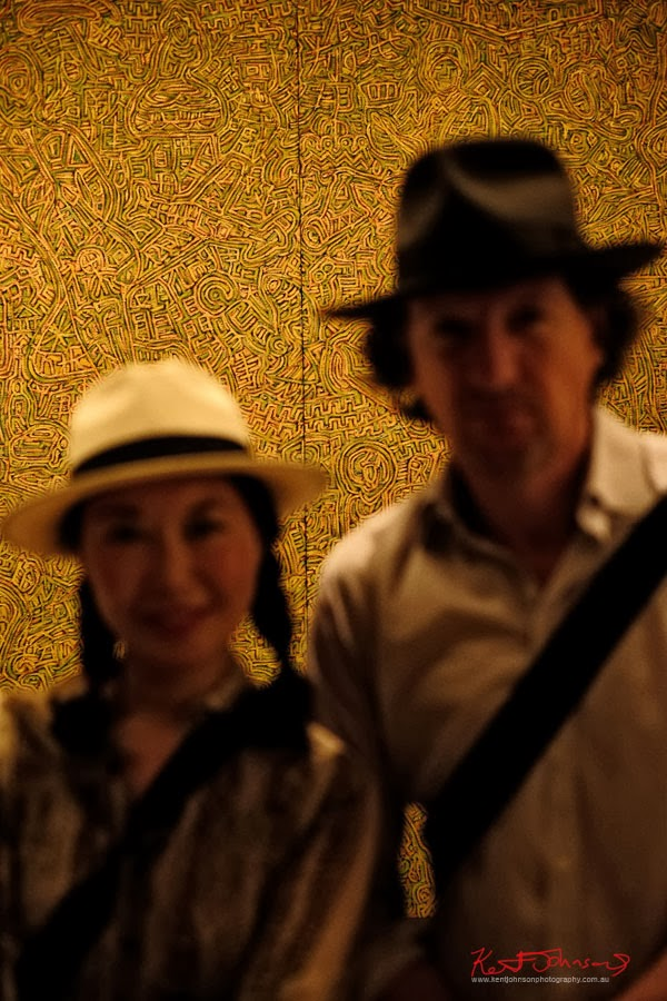 Couple in hats - out of focus with artwork behind - Serve the People art opening at White Rabbit Gallery. Picture by Mike, Newtown Graffiti..
