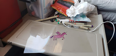 desk space aboard train with drawing of flying unicorn and different pens on table.