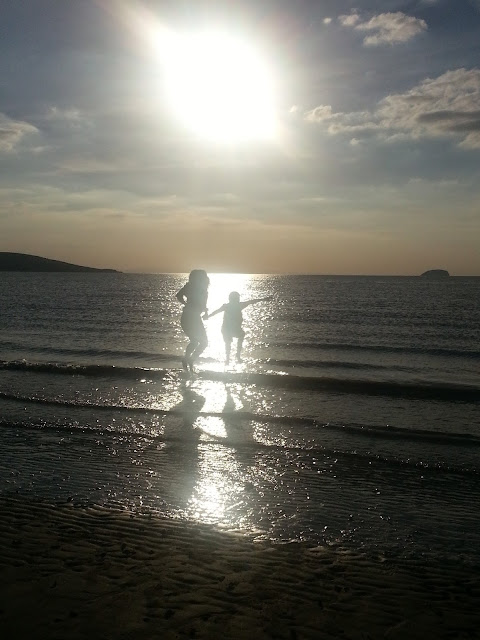Children silhouetted against the sunset, playing in the waves