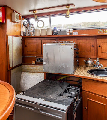 Photo of our galley with the cooker and fridge pulled out