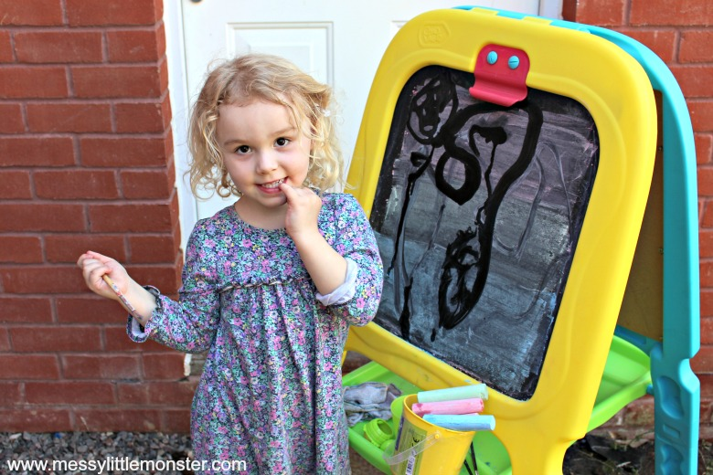 easy outdoor art idea for toddlers and preschoolers - painting with water on a chalkboard