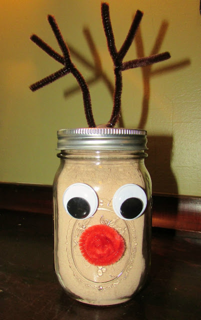 glass jar decorated like Rudolph the red nosed reindeer and filled with hot cocoa mix