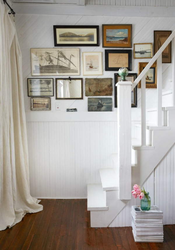 Charming art on gallery wall covered with #beadboard in #cottagestyle stairway on Hello Lovely Studio