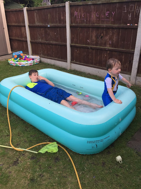 siblings playing in the paddling pool