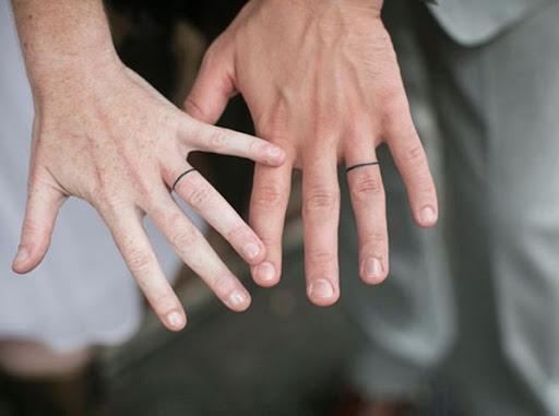 """Finas linhas pretas funcionam como faixas de casamento no anel dedos dos usuários """" esquerda mãos neste tatuagem conjunto."""