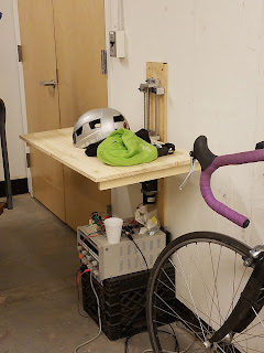 bike helmet and attire piled on desk with motor power supply and cables underneath