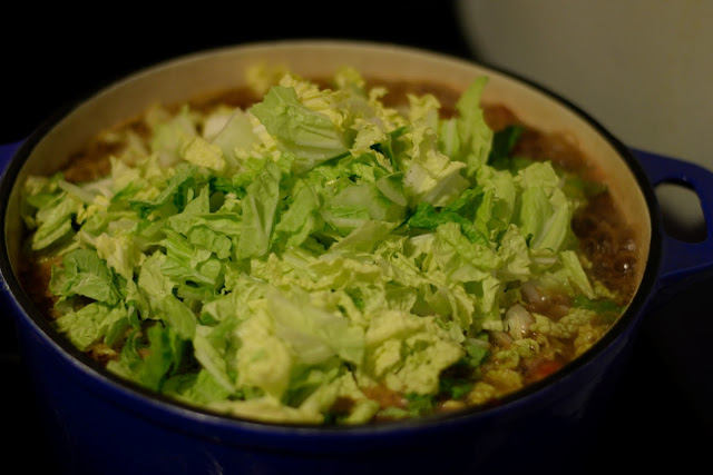 Chopped cabbage being added to the pot.