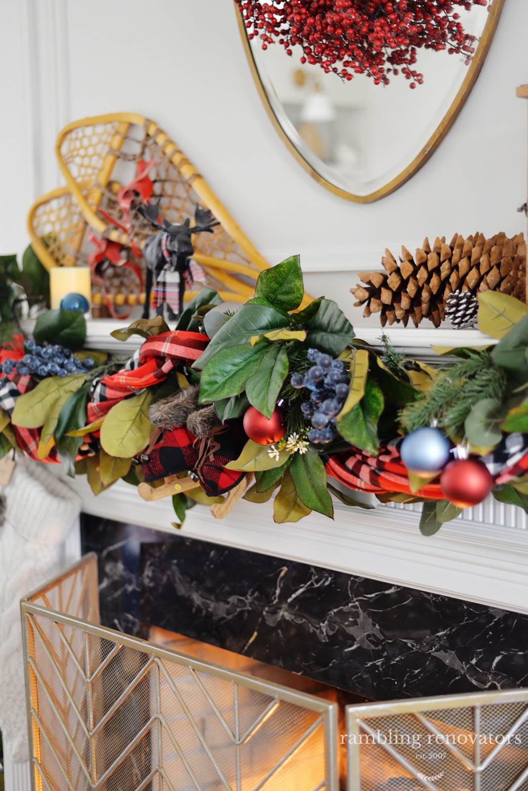 A lush and colourful red and blue Christmas mantel with a plaid scarf, blueberry picks and rustic accents