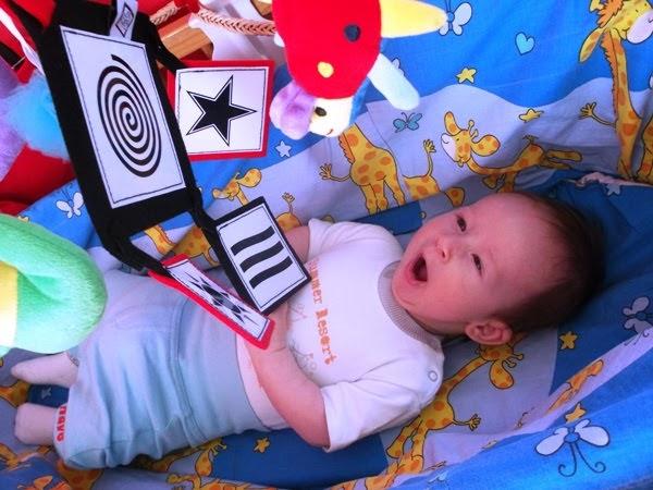 niemowle bawi się w koszu mojżesza
