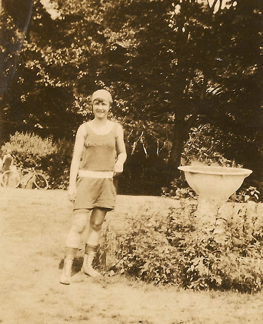 """Young woman in bathing suit, with """"Mickey"""" on her shirt, standing next to som plants. Possible connection to the Dixon family."""