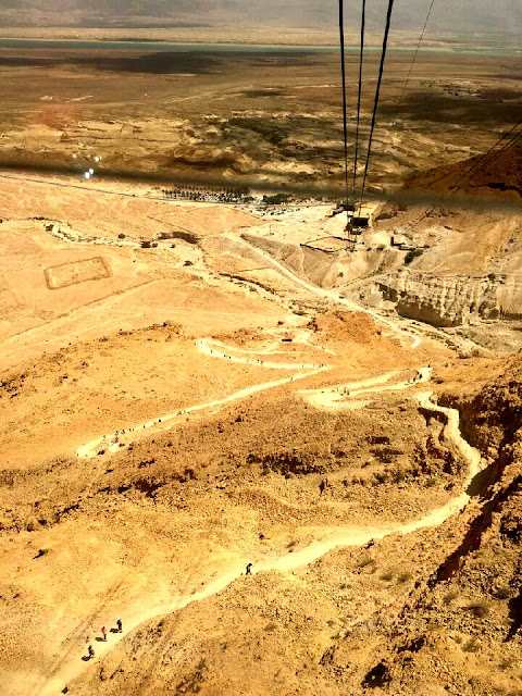 Photo looking down at the Snake Path to get to Masada Israel with the cable cars coming up the mountain