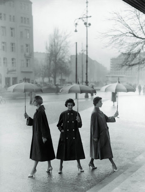 Three women modelling umbrellas in rain