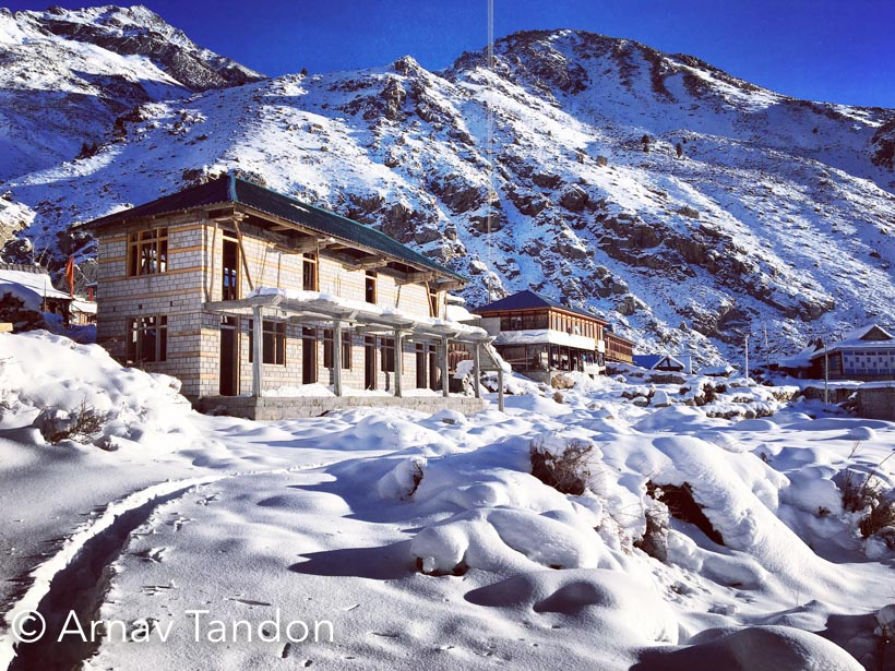 It was 21st feb '2016 the day we reached sangla , the local's recommended us not to travel further because the roads were closed for chitkul but we mandyals always love to do what obstruct others. We took a taxi to chitkul but the driver was little scared off the road conditions.The moment we reached raksham we found the roads are not in proper shape to travel further . So we took a risk and started walking.It was around 10kms that we decided to go by foot .The snow was almost touching our shoes bottom ,but  After few hours the snow started rising from mm to cms .The beauty around the valley was getting more exotic .It took us more than 4hrs to complete the 10kms patch between  raksham and chitkul .This  bridge gave us a hope that we are close to our destination.Finally after the tiring journey we made it toChitkul ,we  had a comfortable stay in HP Pwd resthouse. The best part was that the electricity was on full voltage which kept us warmer in such parky weather  .The next morning we roamed around the chitkul village .My friend decided to take some vitamin D before we walk back 10kms to raksham to catch a bus to reckongpeo.While he was having a sun on his head i decided to have a cup of tea with the local's.Somebody said it true , Chitkul looks best in winters .The only thing I learned from this trip , that  life in winters is really difficult here and I experienced it in this short trip to Chitkul , kinnaur (H.P)