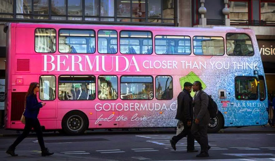 Bright pink and turquoise double decker bus advertising Bermuda