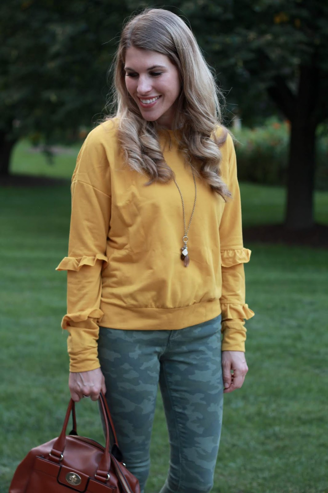 ruffled mustard sweatshirt, camo pants, Tory Burch Miller sandals, cognac crossbody bag