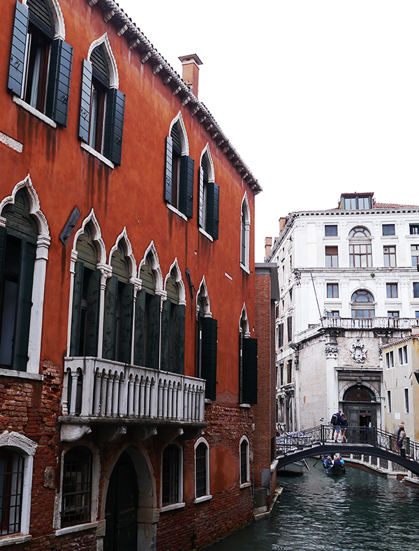 Facade of red building with pointed arch windows next to a canal in Venice, Italy