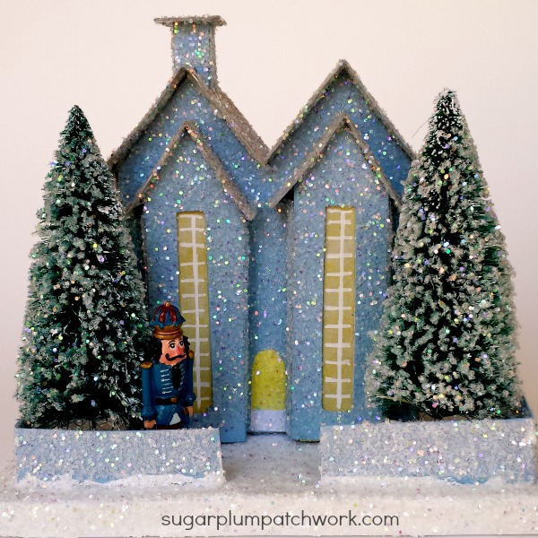 Blue glitter house with trees and toy nutcracker