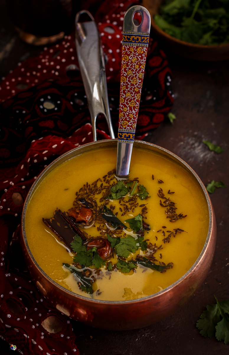 Gujarati Mango Kadhi served in a copper pan and garnished with fresh chopped coriander