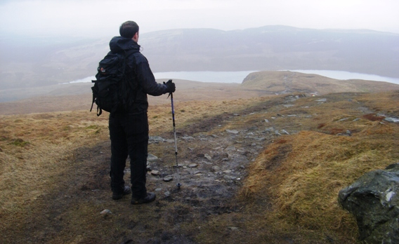 A man standing on a path leading down a hill towards a loch