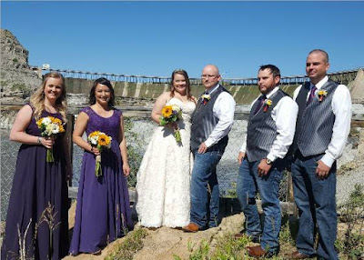 Randy and Dawn with their wedding party posing for a picture with Ryan Dam in the background