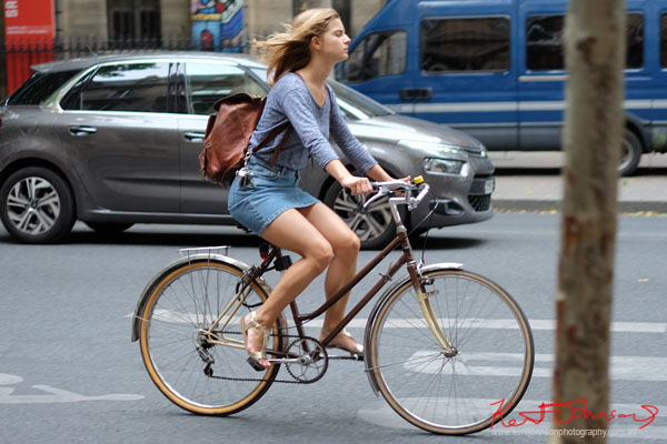 Young blonde woman in gray marle top and denim skirt and silver sandals, leather backpack rides a brown woman's bike.Paris photos by Kent Johnson for Street Fashion Sydney.