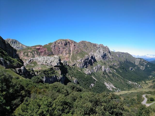 Vista del sendero a la izquierda y el valle desde el Alto de la Farrapona, con la huella roja de la mina de hierro al fondo, arriba, a la izquierda