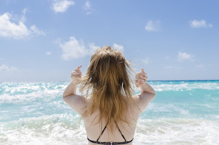 back of woman's head as she feels her hair at beach.jpeg