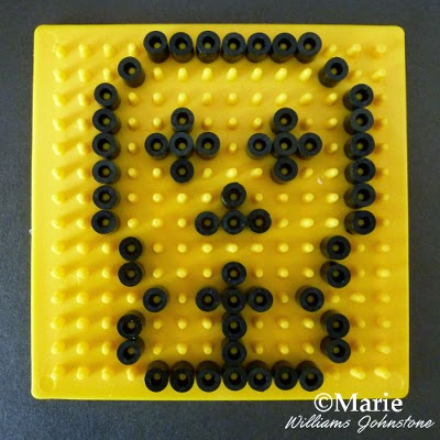 Yellow board with black Perlers on the pegs making a skull face shape